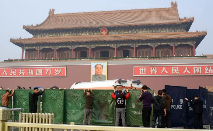 Muncitori mascând scena accidentului din Piaţa Tiananmen, unde o maşină a intrat în plin în mulţime, luând apoi foc.