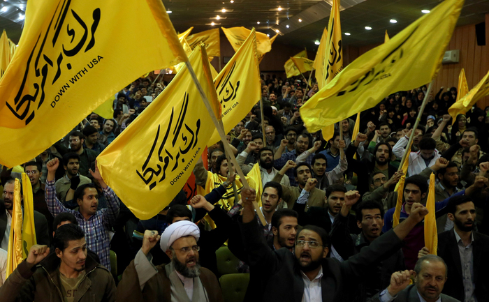 """Extremiştii iranieni flutură steaguri pe care scrie """"Jos cu SUA"""" la fosta ambasadă SUA la Teheran, 2 noiembrie 2013."""