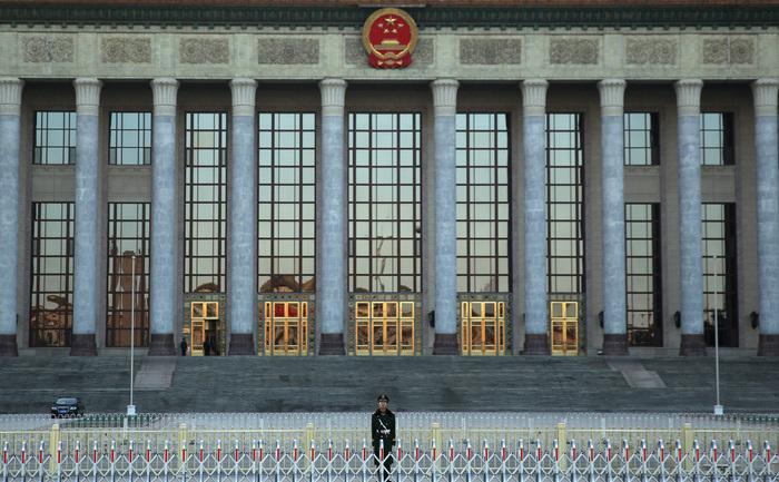 Un ofiţer de poliţie stă de pază în faţa Marii Sălii a Poporului în Beijing, China.