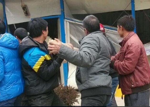 Patru săteni folosesc stâlpi de lemn pentru a sparge birourile Uzinei Electrice Nanshan de pe râul Weijiang în oraşul Guilin, China, 18 noiembrie 2013
