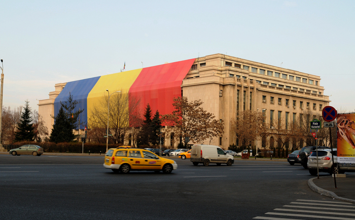 Cladirea Guvernului acoperită de un drapel uriaş.