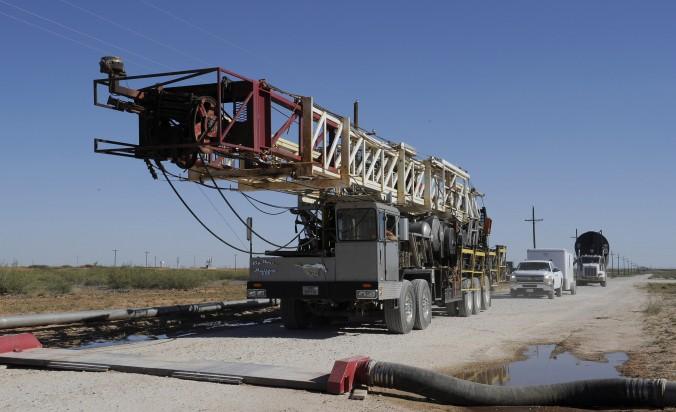 Instalaţii de foraj folosite pentru fracturarea hidraulică, tractate peste un furtun de apă de la un site de foraj, în 24 septembrie 2013, Midland, Texas.