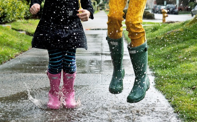 Copii care se joacă în ploaie