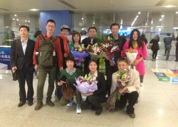 Cetăţeni chinezi urează bun venit avocatului Tang Jitian (spate, al doilea din dreapta) şi avocatului Wang Cheng (spate, al treilea din dreapta) la aeroportul Beijing, pe 6 aprilie.