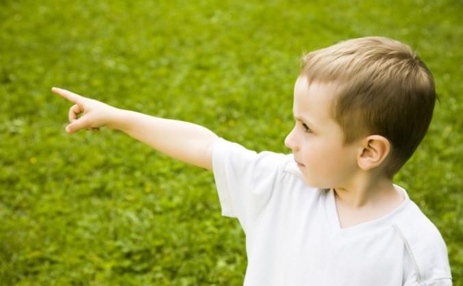 Un băieţel care arată cu degetul.