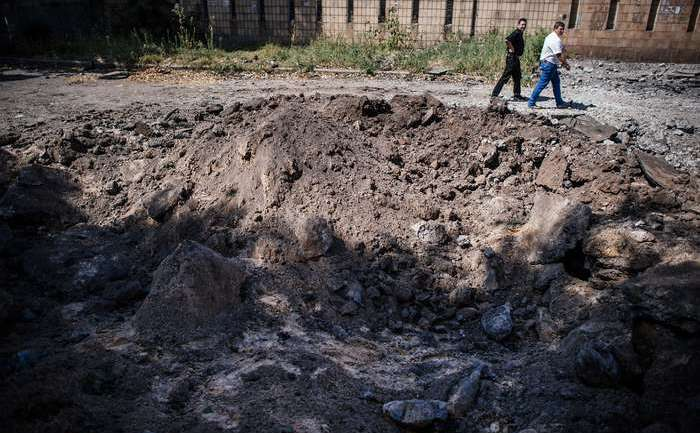 Crater produs de bombardamente aeriene pe o stradă din Doneţk - 6 august 2014