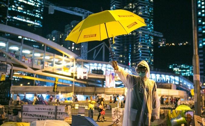 Un activist pro-democraţie stă în faţa complexului guvernamental din Districtul Central al Hong Kong-ului, 9 octombrie 2014.