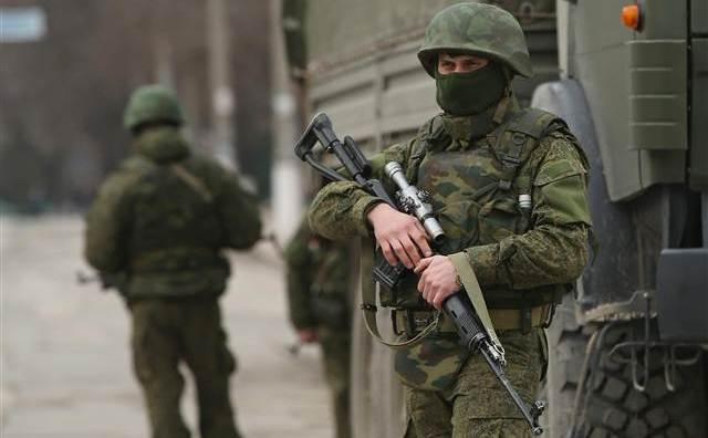 Soldaţi puternic înarmaţi şi fără însemne de identificare stau de pază pe o stradă din centrul oraşului ucrainean Simferopol, 1 martie 2014.