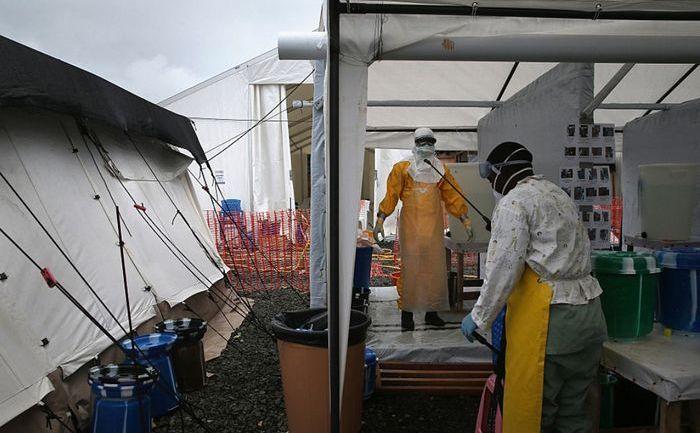 Un angajat în sectorul medical este suspus dezinfectării la un centru de tratament al organizaţiei Doctori Fără Frontiere, după ce a lucrat o oră într-o zonă cu risc ridicat de infectare cu Ebola, 5 octombrie 2014, în Paynesville, Liberia.