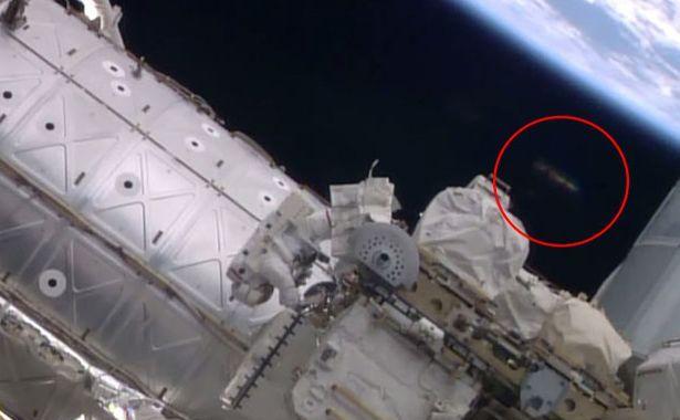 Un posibil OZN surprins de camera Staţiei Spaţiale Internaţionale în timpul unei operaţiuni de întreţinere executate de doi astronauţi.