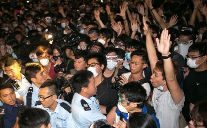 Manifestanţii pro-democraţie de pe bulevardul Lung Wo îşi ridică mâinile în sus pentru a arăta poliţiştilor că sunt neînarmaţi, 16 octombrie 2014, Hong  Kong.