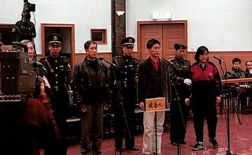 Wang Zhiwen (al treilea din stânga) este adus în faţa instanţei alături de alţi practicanţi Falun Dafa în noapte de 26 decembrie, 1999. Acest proces era menit să-i influenţeze pe ceilalţi practicanţi, contribuind la eforturie care trebuiau să-I determine să renunţe la disciplina spirituală