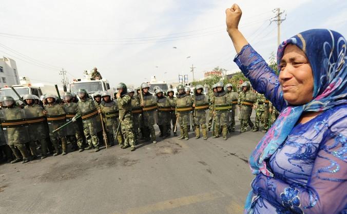 Fortele de ordine chineze se uită la o femeie uigur de etnie musulmană ce protestează în Urumqi, provincia vestică îndepărtată chineză Xinjiang, 7 iulie 2009.