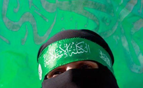 O femeie palestiniană poartă o bandană verde tipică Hamasului.