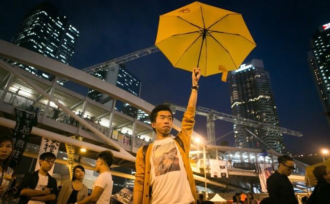 Un protestatar pro-democraţie ţine o umbrelă galbenă în timpul unui miting pe 28 octombrie 2014