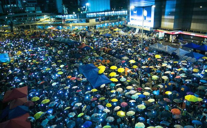 """Mii de oameni """"înarmaţi"""" cu umbrele îşi flutură telefoanele mobile în timp ce este difuzat un cântec despre protest în Districtul Central din Hong Kong, 28 octombrie 2014."""