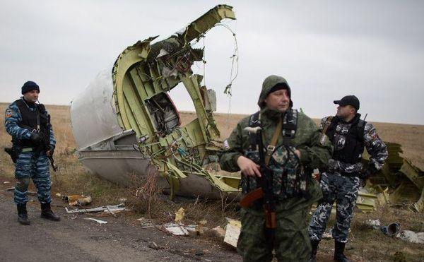 Separatişti proruşi înarmaţi stau de pază în timp ce investigatorii olandezi (care nu apar în imagine) analizează câteva rămăşiţe ale zborului malaezian MH17, la locul prăbuşirii, în apropiere de satul Grabove, 11 noiembrie 2014.