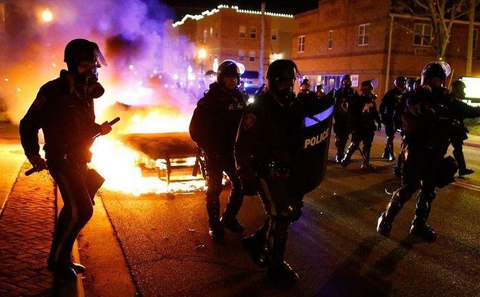 Poliţiştii trec pe lângă o maşină incendiată pe o stradă din oraşul Ferguson, districtul St. Louis, 24 noiembrie 2014.