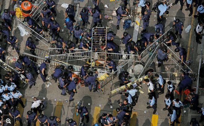Ofiţeri de poliţie înlătură baricade în districtul Mong Kok din Hong Kong, 26 noiembrie 2014.