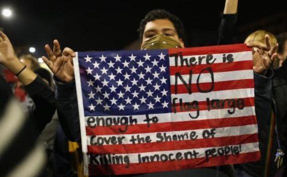 Un manifestant afişează un steag american în timpul unui marş în Berkeley, California, împotriva deciziei marelui juriu din New York de a nu acuza un ofiţer de poliţie implicat în uciderea lui Eric Garner, 7 decembrie 2014.
