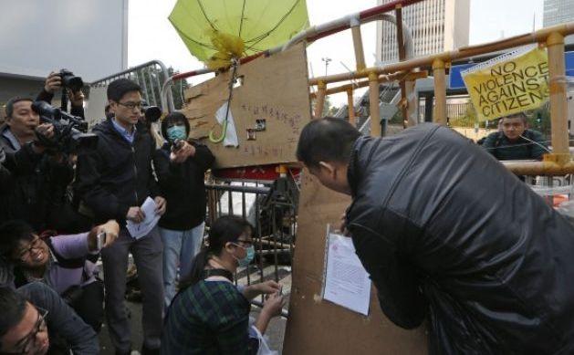 Un oficial lipeşte o hotărâre judecătorească pe o baricadă a manifestanţilor pro-democraţie în faţa sediului guvernului din Hong Kong, 9 decembrie 2014.