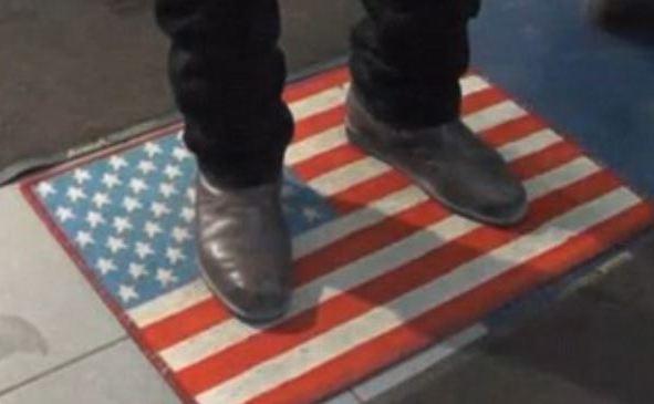 Un client se şterge pe un covor pe care este imprimat un steag american în timp ce intră într-un mall din Moscova.