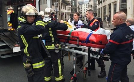 Pompierii transportă pe o targă un bărbat rănit în atacul armat asupra publicaţiei Charlie Hebdo din Paris, 7 ianuarie 2015.