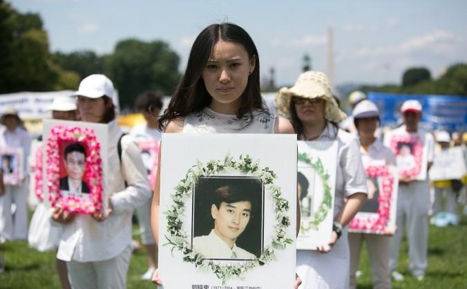 O femeie ţine un portret al unui chinez torturat până la moarte pentru că practica Falun Gong în China, în timpul unui miting din Washington  la 17 iulie 2014
