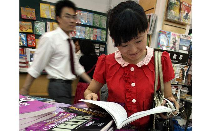 O studentă se uita la manuale în timpul vacanţei de vară, la o librărie din Shanghai pe 16 august 2007