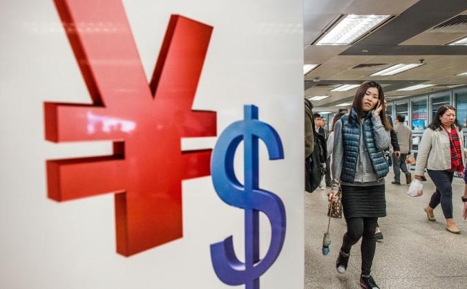 Simbolurile yuanului chinezesc şi dolarului afişat într-un magazin din Hong Kong