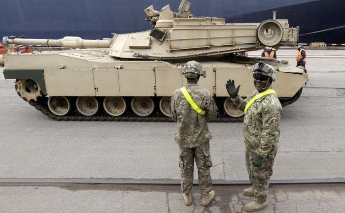 """Soldaţi americani inspectează un tanc de luptă Abrams în portul Riga, 9 martie 2015, pentru trupele americane ce vor fi trimise în regiunea Baltică ca parte a operaţiunii NATO """"Atlantic Resolve""""."""