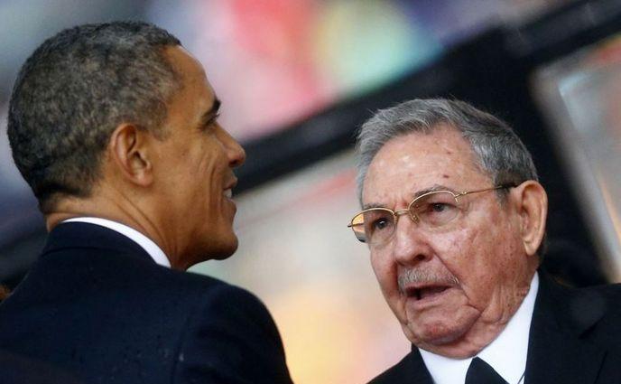 Preşedintele american Barack Obama dă mâna cu omologul său cubanez Raul Castro în Africa de Sud, decembrie 2013.