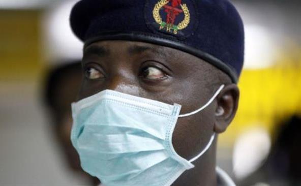 Un  oficial nigerian al sănătăţii poartă o mască de protecţie în timp ce  verifică pasagerii în Aeroportul Internaţional Murtala Muhammed din  Lagos, Nigeria, 4 august 2014.