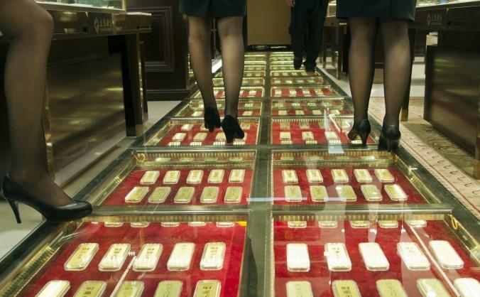Personalul calcă pe un şir de lingouri de aur într-un magazin de aur din Kunming, China, 11 decembrie 2012.
