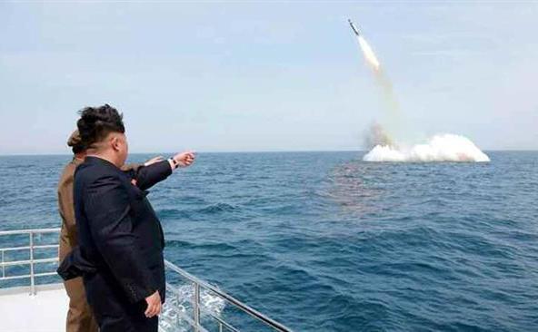 Kim  Jong-un arată înspre ceea ce este considerată a fi o rachetă balistică  lansată dintr-un submarin în apropiere de Sinpo, coasta nord-estică a  Coreei de Nord, 9 mai 2015.