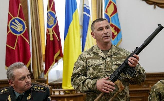 Un  comandant militar ucrainean prezintă, la o conferinţă de presă în 18   mai 2015, o armă găsită asupra unui soldat rus capturat în Ucraina.