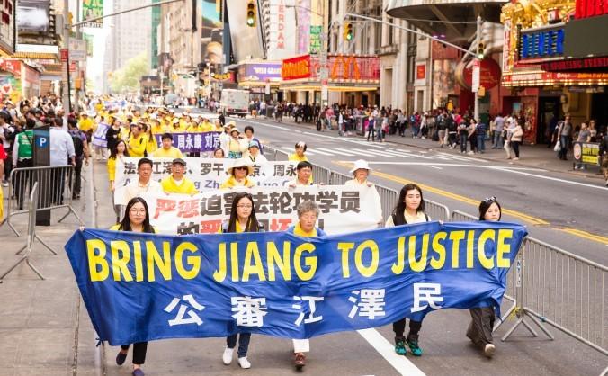 Practicanţi Falun Gong ţinând un banner care-l denunţă pe fostul lider comunist chinez Jiang Ziemin, ca fiind responsabil pentur începerea persecuţiei aderenţilor Falun Gong, în timpul unei parade Falun Gong în Manhattan - 15 mai 2015.