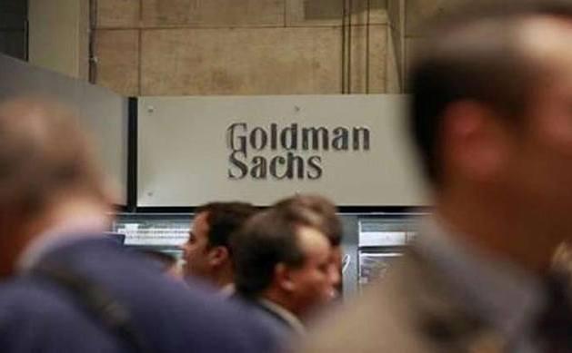 Oamenii trec pe lângă o siglă a Goldman Sachs.