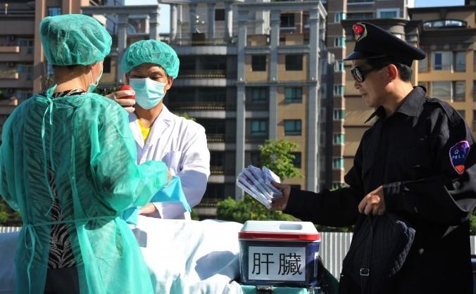 Practicanţi Falun Gong joacă o scenă ilustrând jaful de organe al Chinei comuniste, pe o stradă din Taipei, 20 iulie 2014.