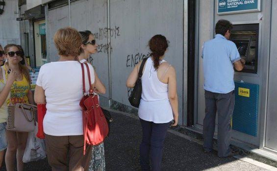 Elenii stau la coadă la un bancomat în Atena.
