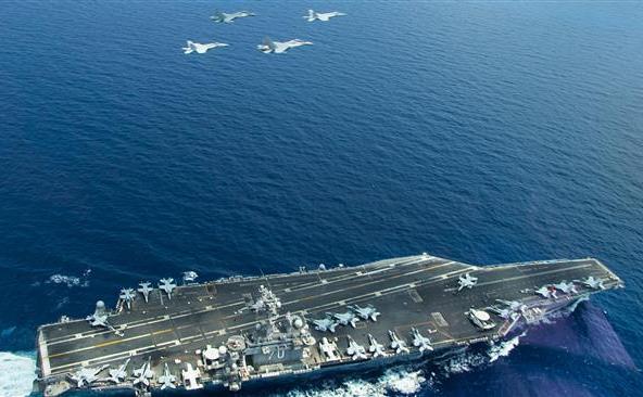 Două avioane de luptă americane F/A-18 Super Hornets şi două avioane de luptă malaeziene zboară deasupra portavionului USS Carl Vinson ce operează în Marea Chinei de Sud, 10 mai 2015.