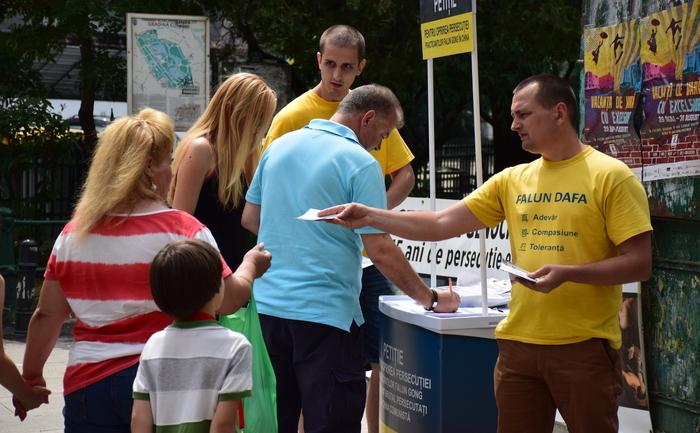Bucureşteni semnând petiţia pentru încetarea genocidului pornit de Partidul Comunist Chinez împotriv practicanţilor Falun Gong, 19 iulie 2015