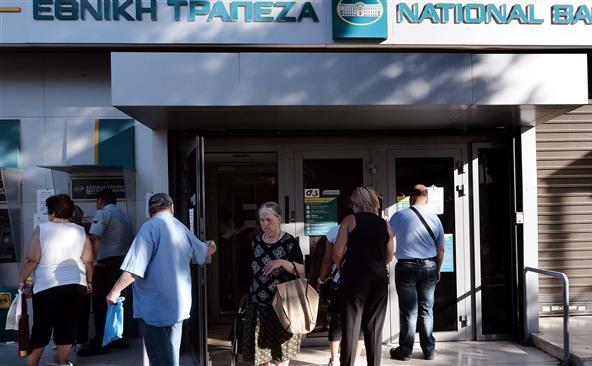 Cetăţeni greci stau în faţa unei filiale a Băncii Naţionale din Atena, 20 iulie 2015.