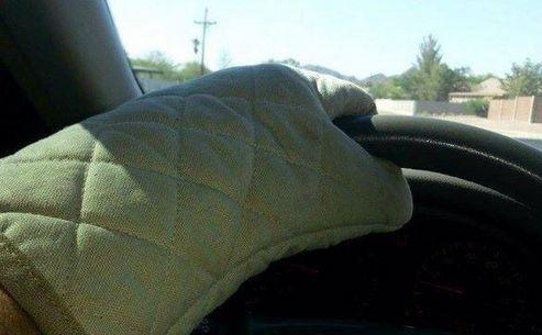 Un cipriot îşi protejează mâinile cu mănuşi de cuptor de volanul încins al maşinii.
