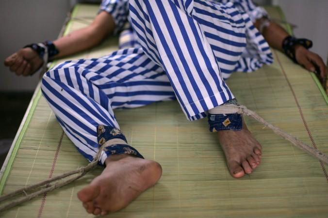 Un bolnav psihic cu mâinile şi picioarele legate la Spitalul de Boli Mintale Anxian, din provincia Sichuan, China, la 24 august 2008