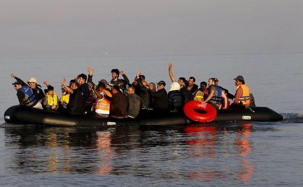 Refugiaţi sirieni într-o barcă pneumatică se bucură în timp ce ajung pe insula elenă Kos.