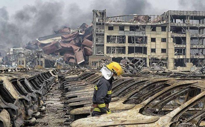 Un pompier chinez trece printre maşinile carbonizate de explozia depozitului din oraşul Tianjin, 12 august 2015.