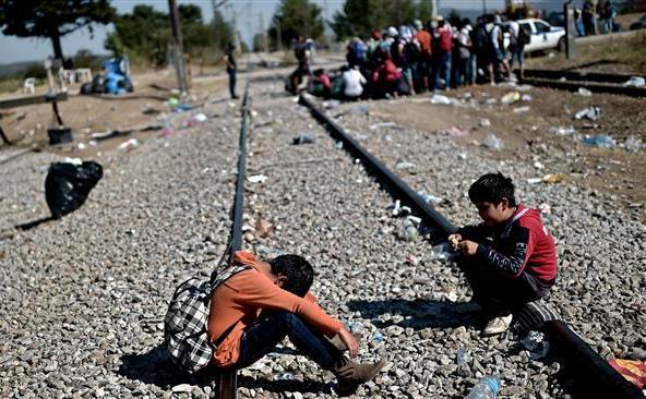 Refugiaţi copii stau pe o cale ferată la un punct de frontieră dintre Grecia si Macedonia, lângă satul elen Idomeni, 29 august 2015.
