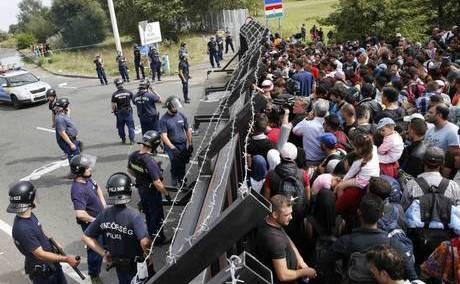 Refugiaţii stau în faţa unei bariere la graniţa sârbo-ungară, în apropiere de satul Hordos din Serbia, 15 septembrie 2015.