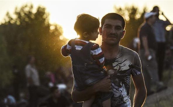 Un refugiat sirian îşi ţine fiul în braţe în drumul lor spre graniţa dintre Turcia şi Bulgaria, în oraşul Edirne din nord-vestul Turciei, 15 septembrie 2015.